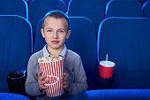 Handsome kid looking at camera, posing in cinema.