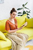 attractive young woman reading book while sitting on bright yellow sofa