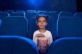 Pretty cute girl sitting with popcorn bucket in cinema.