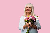 cheerful senior woman holding bouquet of flowers isolated on pink