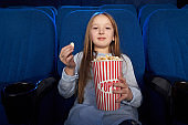 Pretty girl eating popcorn, watching film in cinema.