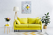 interior of cozy living room with bright yellow elements, decor and retro telephone