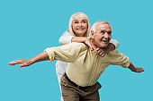happy retired man with outstretched hands near cheerful wife isolated on blue
