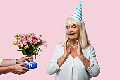 cropped view of senior man giving presents to surprised wife in party cap isolated on pink