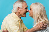 happy retired man looking at cheerful wife and smiling isolated on blue