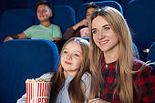 Pretty mother and daughter watching film in cinema.