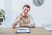 happy recruiter pointing with finger while sitting near clipboard and pen and looking at camera