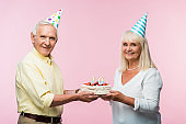 happy senior couple in party caps holding birthday cake isolated on pink