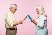 side view of happy senior couple reading books while standing isolated on pink