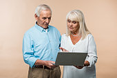 retired woman gesturing while looking at laptop near senior husband isolated on beige