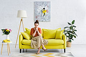 pensive elegant young woman sitting with crossed legs and clenched hands on yellow sofa in living room