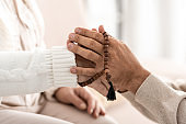 cropped view of senior man with rosary breads holding hands with wife