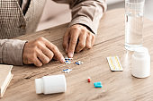cropped view of retired man matching puzzle pieces on table