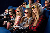 Crowd watching 3D movie in theatre.