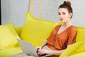 elegant young woman sitting on yellow sofa, using laptop in living room and looking at camera