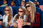 Mother and daughter watching 3D movie in cinema.