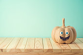 Halloween holiday concept with cute funny pumpkin decor on wooden table