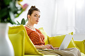 selective focus of fashionable young woman in pearl necklace sitting on yellow sofa and using laptop