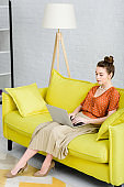 elegant young woman sitting on yellow sofa and using laptop in living room