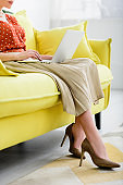cropped view of young woman in heeled shoes sitting on yellow sofa and using laptop