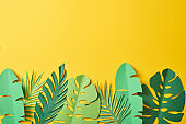 top view of paper cut green palm leaves on yellow background with copy space