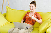 happy elegant young woman sitting on yellow sofa, using laptop in living room and showing thumb up