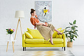 side view of elegant young woman levitating in air and talking on vintage phone in living room