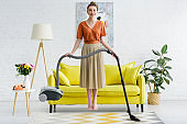 elegant smiling barefoot young woman levitating in air and holding vacuum cleaner