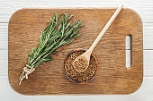 top view of rosemary and coriander in bowl with wooden spoon on chopping board