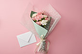 top view of beautiful tender flower bouquet and white envelope isolated on pink