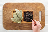 cropped view of woman touching wooden bowls with bay leaves and black pepper on chopping board
