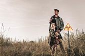 handsome man with gun near cute kid with teddy bear and toxic symbol, post apocalyptic concept