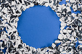 Top view of silver circle made of confetti on blue background