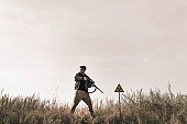 man holding gun near toxic symbol in field, post apocalyptic concept