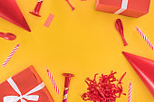 Red birthday party objects on yellow background