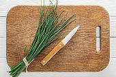 top view of green onion and knife on wooden chopping board
