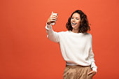 happy woman in autumnal outfit taking selfie with hand in pocket isolated on orange