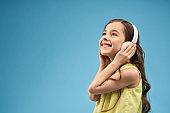 Side view of cheerful girl in headphones listening music