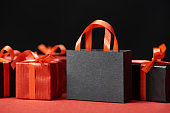red presents and shopping bag with copy space isolated on black