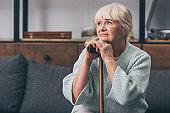sad senior woman with walking cane at home