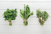 top view of green parsley, basil and thyme on white wooden table