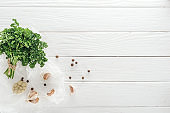 top view of garlic cloves, black pepper and parsley on white wooden table