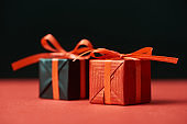 selective focus of gift boxes with red ribbons isolated on black
