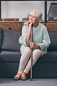 upset senior woman with walking cane sitting on sofa at home