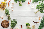 top view of green herbs and spices on white wooden table with copy space