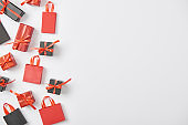 top view of black and red presents and shopping bags on white background