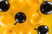 Top view of yellow and black balloons on bright background