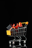 small gifts and shopping bag in decorative trolley isolated on black