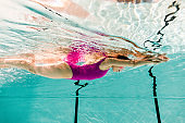 woman swimming underwater in swimming pool with blue water