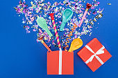 Red gift box and various party decor on blue background